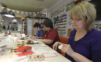 Sylvia Rudkevich, Joanne Millar and Marilyn Whatman (from left) make Christmas cards at Scrapbookers Anonymous on Portage Avenue in Winnipeg, Man., on Wed., Dec. 10, 2014, that will be given to seniors. Kevin King/Winnipeg Sun/QMI Agency