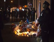 Police stand solemn vigil late at night at a makeshift memorial at the site where two police officers were shot in the head in the Brooklyn borough of New York, December 21, 2014. REUTERS/Carlo Allegri
