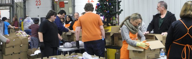 Volunteers worked in assembly-line fashion to pack and load more than 2,200 boxes of food for needy families for this year's delivery of Christmas Baskets.