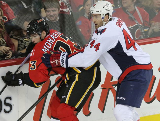 Calgary Flames forward Sean Monahan is taken into the boards by  Washington Capitals defenceman Brooks Orpik at the Saddledome in Calgary on October 25, 2014. (Mike Drew/Calgary Sun/QMI Agency)
