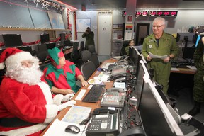 Chris Procaylo/QMI Agency Santa and one of his elves get their pre-flight operational briefing from Lieutenant-Colonel Darrell Marleau, Combat Operations Division Chief (left),  before their flight through Canadian Airspace.