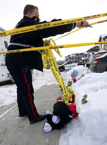 A police officer cuts down some of the tape surrounding a memorial. Police investigates a multiple murder scene at a home on 83 st and 180 ave in Edmonton, Alta., on Wednesday Dec. 31, 2014. Perry Mah/Edmonton Sun/QMI Agency