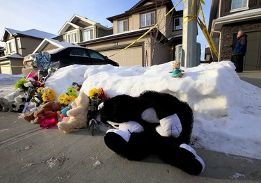 A memorial of flowers and toys are placed in front of a house. Police investigates a multiple murder scene at a home on 83 st and 180 ave in Edmonton, Alta., on Wednesday Dec. 31, 2014. Perry Mah/Edmonton Sun/QMI Agency