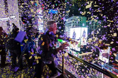 Confetti engineer Norm Larsen tosses confetti onto revellers from the roof of the Marriott Marquis hotel during New Year's Eve celebrations in Times Square in New York December 31, 2014. (REUTERS/Keith Bedford)