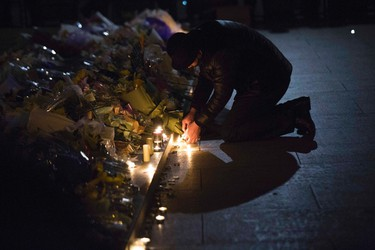 A man lights candles during a memorial ceremony for people who were killed in a stampede incident during a New Year's celebration on the Bund, in Shanghai January 1, 2015. REUTERS/Aly Song