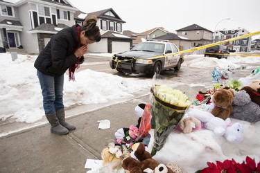 Anne Nguyen, a neighbour, prays for the seven members of a family slain outside of their former home at 180A Avenue and 83 Street in Edmonton, Alta., on Thursday, Jan. 1, 2015. The slayings occurred on Dec. 29, 2014.  Sources say that 53-year-old Phu Lam is the killer; he later committed suicide inside a Fort Saskatchewan restaurant. Ian Kucerak/Edmonton Sun/ QMI Agency