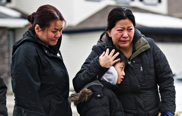 People, including a woman and child identified as the ex-wife and son of Viet Nguyen, right, visit the memorial at the home where seven people were murdered last week in Edmonton, Alta., on Thursday, Jan. 1, 2015. Codie McLachlan/Edmonton Sun/QMI Agency