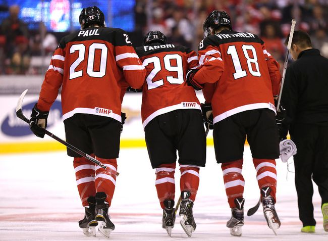 Canada forward  Robby Fabbri (centre) is helped off the ice by teammates after he was injured during the team's World Junior Hockey Championship quarterfinal game against Denmark at the Air Canada Centre in Toronto, Jan. 2, 2015. (CRAIG ROBERTSON/QMI Agency)
