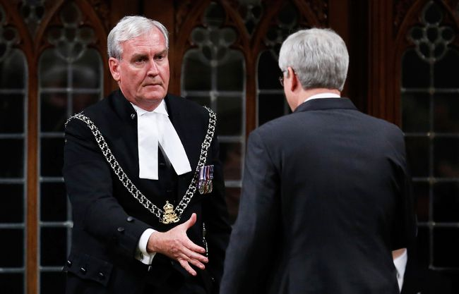 Prime Minister Stephen Harper shakes hands with Sergeant-at-Arms Kevin Vickers in the House of Commons in Ottawa October 23, 2014. Vickers was being thanked for shooting the suspect during a shooting incident Thursday after a gunman killed a soldier and rampaged through parliament before being shot dead. REUTERS/Chris Wattie