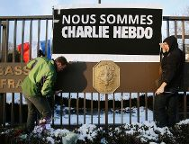 """A sign reading """"We are all Charlie Hebdo"""" is erected by embassy personnel at the front gate of the French Embassy in Washington"""