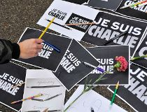 """A man puts a pencil on placards reading """"I am Charlie"""" during a minute of silence for the victims of Wednesday's shooting at the Paris offices of weekly newspaper Charlie Hebdo in Ljubljana"""