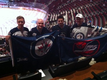 Jets fans hold up flags in a suite at the Gila River Arena in Glendale, Arizona, during the Jan. 8, 2015 game between the Winnipeg Jets and the Arizona Coyotes. TED WYMAN/Winnipeg Sun/QMI Agency