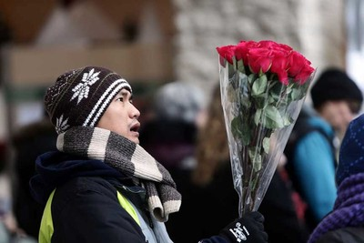 A man checks his floweers before a vigil for the mass murder victims at City Hall in Edmonton, Alta., on Saturday Jan.10 2015. Perry Mah/Edmonton Sun/QMI Agency