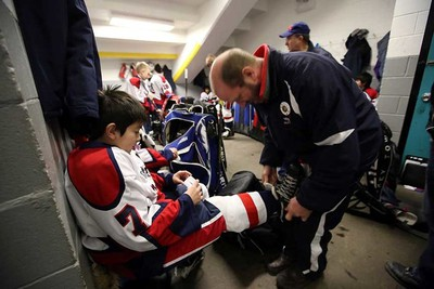 A coach helps a player with his skates before the game. The North East Zone Eagles play their Minor Hockey Week game at South Side Arena against a Millwoods team in Edmonton, Alta., on Saturday Jan.10, 2015. Perry Mah/Edmonton Sun/QMI Agency