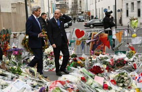 U.S. Secretary of State John Kerry (L) walks with French Foreign Minister Laurent Fabius through a memorial at the site of an attack at the Charlie Hebdo newspaper in Paris Jan. 16, 2015. REUTERS/Rick Wilking