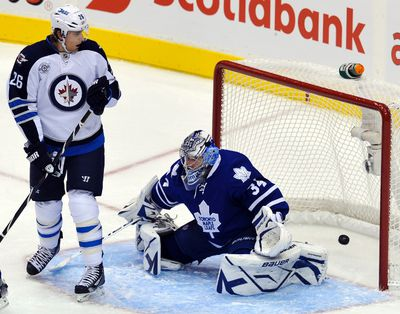 Winnipeg Jets forward Blake Wheeler (L) watches a goal by teammate Tobias Enstrom get past Toronto Maple Leafs goalie James Reimer (R) during the first period of their NHL hockey game in Toronto October 19, 2011.