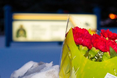 Fresh flowers were lain outside of the St. Albert RCMP detachment at 96 Bellerose Drive in St. Albert, Alta., on Saturday, Jan. 17, 2015. Two officers were shot at the Apex Casino in the city near Edmonton in the early morning hours of Jan. 17 by a suspect police confirm is deceased. Ian Kucerak/Edmonton Sun/ QMI Agency