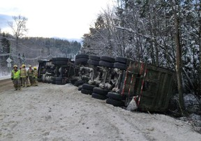 Firefighters survey the scene of a tractor-trailer rollover along Hwy. 309 near l'Ange Gardien on Monday. (MRC des Collines Police submitted image)