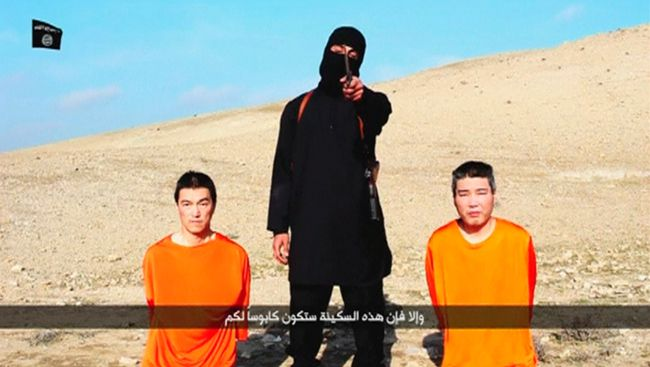 """A masked person holding a knife speaks as he stands in between two kneeling men in this still image taken from an online video released by the militant Islamic State group on January 20, 2015. The militant Islamic State group released the online video on Tuesday purporting to show two Japanese captives and threatening to kill them unless it received $200 million in ransom. The black-clad figure with the knife, standing in a barren landscape along with two kneeling men wearing orange clothing, said the Japanese public had 72 hours to pressure their government to stop its """"foolish"""" support for the U.S.-led coalition waging a military campaign against Islamic State. The militant, who spoke in English, demanded """"200 million"""" without specifying a currency, but an Arabic subtitle identified it as U.S. dollars. The footage named the men as Haruna Yukawa and Kenji Goto.  REUTERS/Social media website"""
