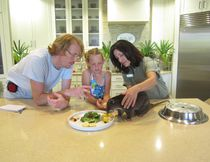 Kyle, left, and Rebecca Hannon with animal educator Joilee Hazley, right, and Burko, a ground cuscus marsupial found in New Guinea and the Aru Islands. BUSCH GARDENS TAMPA PHOTO