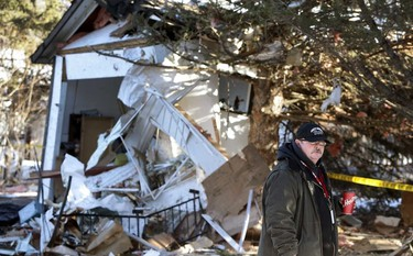 Randy Johnston walks past the damage to his home. Emergency crews are scouring the fiery scene of a Thursday morning house explosion in Morinville.  Emergency responders were call to the scene at 106 Pine Sands Estates about 7:30 a.m. near Morinville , Alberta on Wednesday Jan.21, 2015. Perry Mah/Edmonton Sun/QMI Agency
