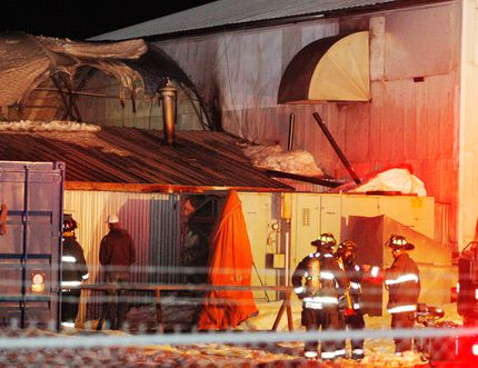 County of Grande Prairie Fire Service firefighters and a bystander survey the damage following a structure fire at a property at 103 Street and 144 Avenue, in the Highway 43 West Industrial Park in the County of Grande Prairie on Wednesday. Tom Bateman/Daily Herald-Tribune