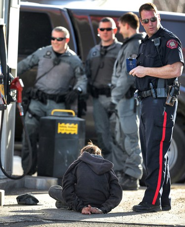 One of two young suspects is taken into custody by police at the 7-Eleven/Petro-Canada in Calgary, Alta., on Jan. 21, 2015. (Al Charest/QMI Agency)