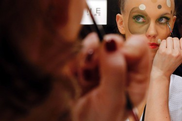 A model has her makeup done backstage before she presents a makeup creation during a show by Maybelline New York at the Berlin Fashion Week Autumn/Winter 2015 in Berlin on Jan. 19, 2015. (REUTERS/Fabrizio Bensch)