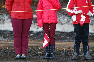 A family waits with Canadian flags for the start of the funeral procession for RCMP Const. David Wynn in St. Albert, Alta., on Monday, Jan. 26, 2015. The regimental funeral is being held at Servus Place in St. Albert. Wynn was killed in a shooting on Jan. 17, 2015 while attempting an arrest at Apex Casino. Ian Kucerak/Edmonton Sun/ QMI Agency