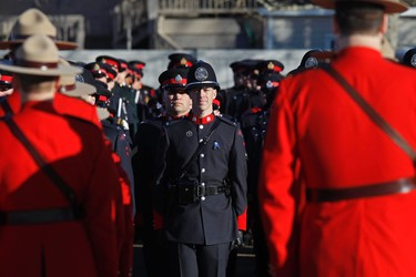 Members of the RCMP march along with 1000's of members of other police departments stand at attention before the start of the funeral procession for RCMP Const. David Wynn in St. Albert, Alta., on Monday, Jan. 26, 2015. The full regimental funeral is being held at Servus Place in St. Albert. Wynn was killed in a shooting on Jan. 17, 2015 while attempting an arrest at Apex Casino. Ian Kucerak/Edmonton Sun/ QMI Agency
