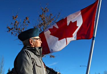 Bill Lawrence of Edmonton holds a Canadian flag during the funeral procession along Poirier Avenue for slain RCMP officer Cst. David Wynn in St. Albert, Alta., on Monday, Jan. 26, 2015. Codie McLachlan/Edmonton Sun/QMI Agency