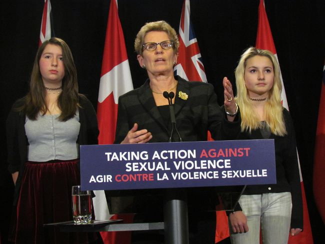 Premier Kathleen Wynne, with Toronto students Tessa Hull (left) and Lia Valente, announces that the new sex education curriculum will address the issue of consent Monday, Jan. 26, 2015. (Toronto Sun/Antonella Artuso)