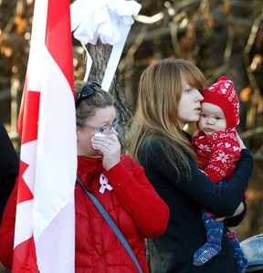 A woman wipes a tear away as a mother holds her child as members of the RCMP and members of other police departments walk in the funeral procession for RCMP Const.. David Wynn in St. Albert on Monday. (IAN KUCERAK/Edmonton Sun)