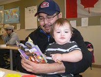 Cumberland College student, Chris (left) reading to his son, Shadaryus (right) at the Nipawin campus yesterday afternoon.