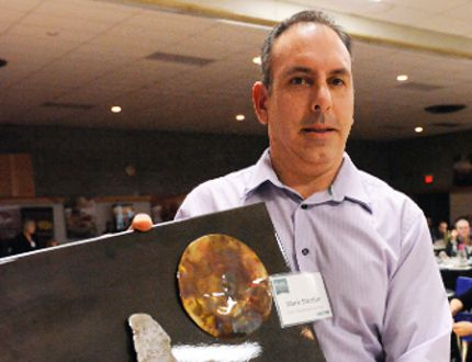 Mike Stortini, one of the partners in David's Restaurant in Port Dover, was named Norfolk County's entrepreneur of the year on Wednesday. He holds a piece of art made by Cole Talbot, who was named the county's young entrepreneur of the year. (DANIEL R. PEARCE Simcoe Reformer)