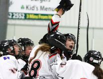 Cochrane Rockies Midget 'B' girls team celebrates Summer Gibbons (18) goals during their 3-2 victory over Lethbridge, Jan. 18. Gibbons scored all three goals as Katie Goetjen raises her arm in jubilation, before she was slew-footed and knocked out of the game with an injury, one of several the team incurred during the game.
