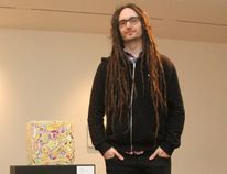 "Visual artist Jeremy Hof stands beside his piece, ""Marble Cube,"" at the Art Gallery of Grande Prairie on Wednesday. Hof's exhibit runs to April 26. It features abstract paintings and sculptures, made by layering acrylic paint. Alexa Huffman/Daily Herald-Tribune"