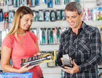 Couple buying flashlight in hardware store with smartphone