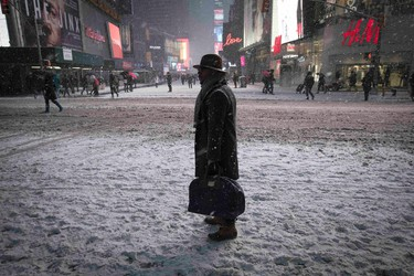 A man stands in falling snow on West 42nd street in Times Square in New York, January 26, 2015.  REUTERS/Mike Segar