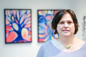 Brenda Isaak Takao stands in front of some of her paintings during the opening of her exhibit 'Organic' on January 24, 2015. The artist's show also predominantly features metal sculptures. John Stoesser photo/QMI Agency.