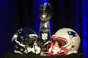 The Vince Lombardi Trophy is displayed between the helmets of the Seattle Seahawks (L) and New England Patriots prior to a joint press conference with Head Coach Bill Belichick of the New England Patriots and Head Coach Pete Carroll of the Seattle Seahawks prior to the upcoming Super Bowl XLIX on January 30, 2015 in Phoenix, Arizona.   (Rob Carr/Getty Images/AFP)