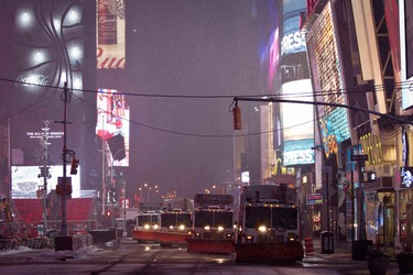 A row of snow plows make their way through Times Square during a snow storm in the early morning hours in the Manhattan borough of New York, February 2, 2015.     (REUTERS/Carlo Allegri)