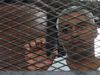 Al Jazeera journalist Mohamed Fahmy stands behind bars at a court in Cairo in this May 15, 2014 file photo. (REUTERS/Stringer/Files)