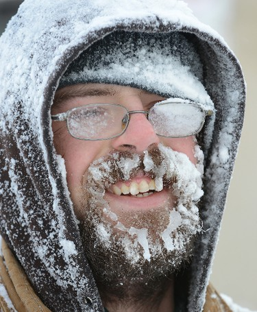 Lloyd Stamas is coated in snow and ice after using a snowblower to clear the sidewalk in front of Centennial Hall in London, Ont., February 2, 2015. (MORRIS LAMONT/QMI Agency)