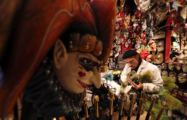"""Iranian mask artisan Hamid works on a carnival mask in his shop """"Ca' del Sol""""  near St. Mark's square during the first day of carnival in Venice February 1, 2015. REUTERS/Stefano Rellandini"""