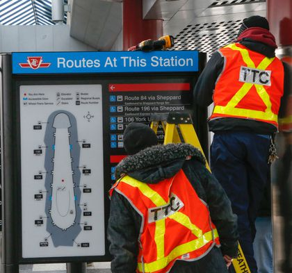 TTC employees work to remove the controversial sign at Downsview station. (DAVE THOMAS/Toronto Sun)