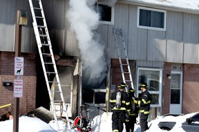 Woodstock firefighters gather in front of a Springbank Gardens townhouse off of Springbank Ave. and Devonshire Ave., where a fire completely destroyed the inside of the residence. (BRUCE CHESSELL/Sentinel-Review file photo)