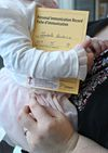 Melanie Lauziere holds her daughter Isabelle after she got her immunized at the Montfort Hospital on Friday Feb 13, 2015. Isabelle holds her immunization record.  Tony Caldwell/Ottawa Sun/QMI Agency