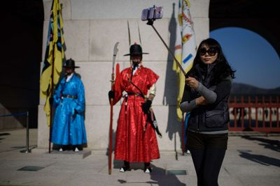 In a photo taken on November 26, 2014 a woman uses a 'selfie stick' to take a photo before the gates of the Gyeongbokgung palace in central Seoul. In South Korea anyone selling an unregistered bluetooth-enabled selfie stick could face a 27,000 US dollar fine or up to three years in prison, the Science Ministry announced last week. The focus of the ministerial crackdown are those models that come with bluetooth technology, allowing the user to release the smartphone shutter remotely, rather than using a timer. As such they have to be tested and certified to ensure they don't pose a disruption to other devices using the same radio frequency. AFP PHOTO / Ed Jones