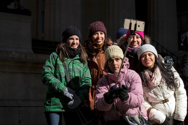 Tourists use a selfie-stick for a photograph on a cold and windy day in New York's financial district February 13, 2015. Bitter cold temperatures were expected to grip much of the northeast U.S. Friday and through the weekend as some of the coldest air of the season moved into the region according to local reports. REUTERS/Brendan McDermid
